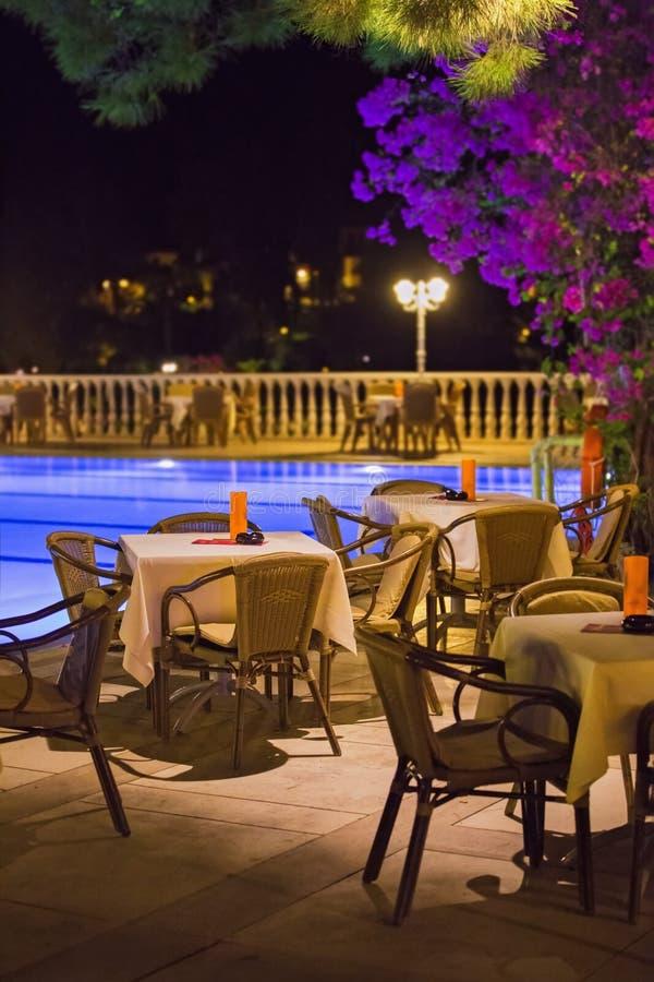 El café de la noche, las tablas vacías sirvió para la cena, velas, luces, por la piscina en el jardín con las palmeras y las flor imagenes de archivo