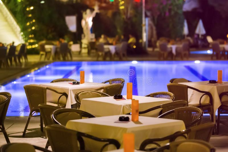 El café de la noche, las tablas vacías sirvió para la cena, velas, luces, por la piscina en el jardín con las palmeras y las flor fotos de archivo libres de regalías