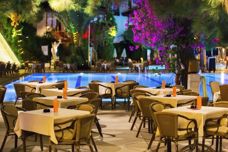 El café de la noche, las tablas vacías sirvió para la cena, velas, luces, por la piscina en el jardín con las palmeras y las flor foto de archivo libre de regalías