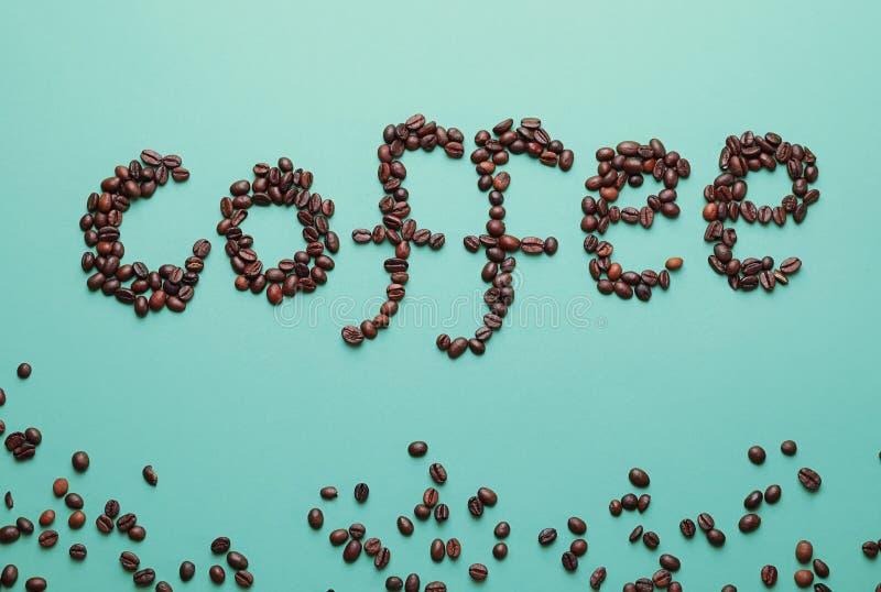 El café de la palabra hizo de habas en fondo del color foto de archivo libre de regalías