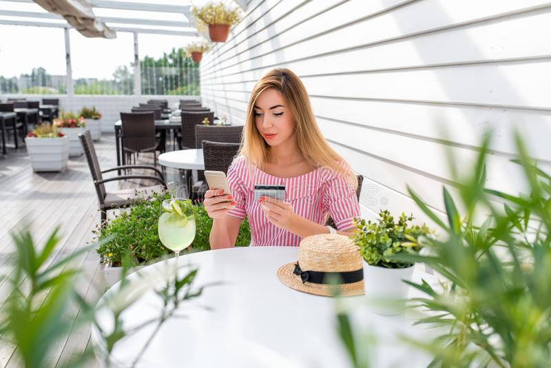 El café del verano de la mujer, teléfono de la tarjeta de crédito de la mano, paga la compra, pide mercancías, escribe del dinero foto de archivo