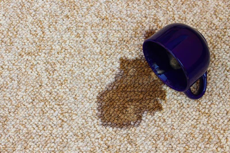 El café desbordó la taza en la alfombra foto de archivo