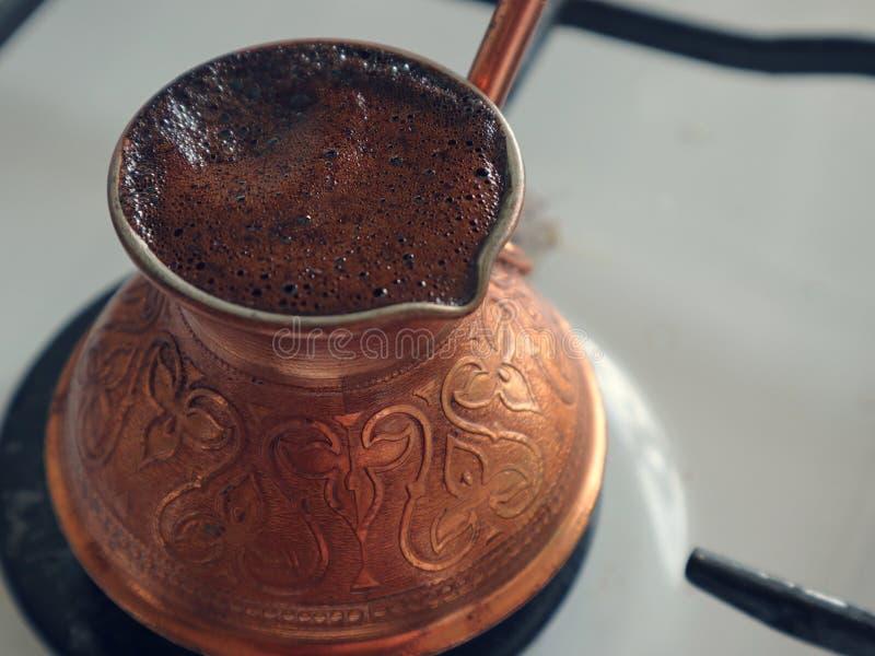 El caf? est? preparado en un turco de cobre en la estufa de gas foto de archivo