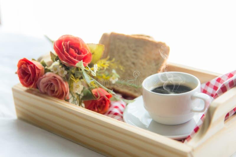 El café fresco de la mañana con pan, subió en bandeja en la cama imagen de archivo