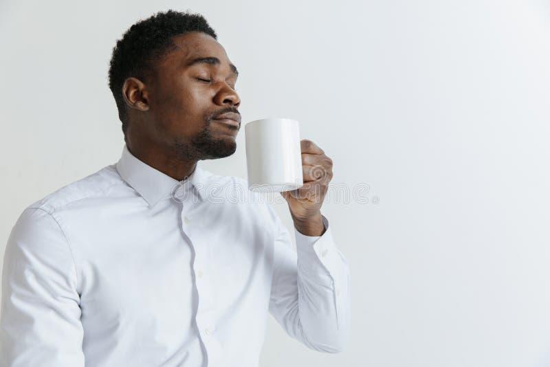 El café hace su día Café de consumición del hombre africano hermoso joven y mirada lejos imagen de archivo libre de regalías