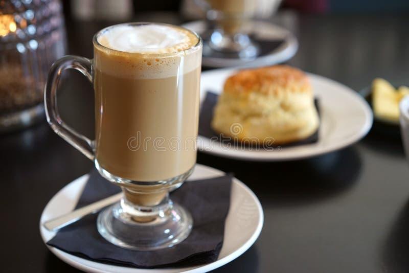 El café irlandés y el scone hace mi día foto de archivo