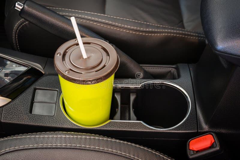 El café o el té asalta el verde puesto en la consola del vehículo en coche de lujo moderno imagenes de archivo