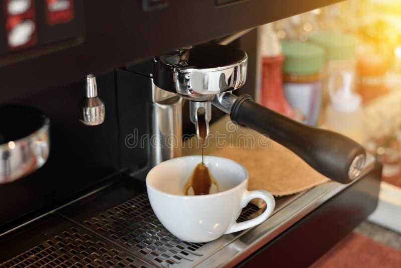 El café sólo caliente se vierte en una taza blanca imagenes de archivo