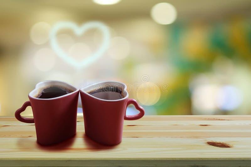 El café sólo en forma rosada del corazón de dos tazas con humo es una forma del corazón en piso de madera y fondo colorido del bo imagen de archivo