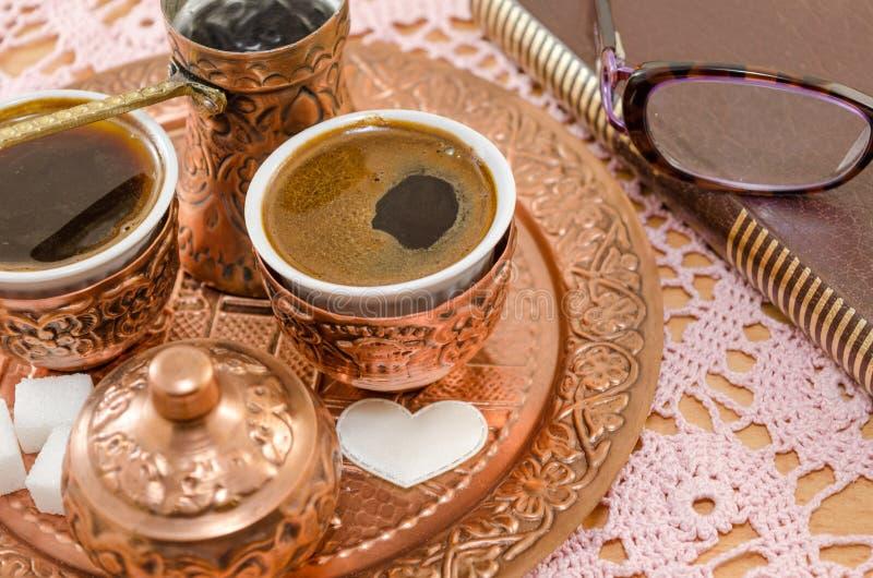 El café sirvió en la cerámica de cobre y un libro imagenes de archivo