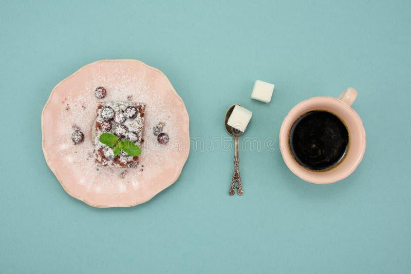 El café y el arándano frescos se apelmazan en plato del vintage en fondo de la turquesa Visión superior foto de archivo