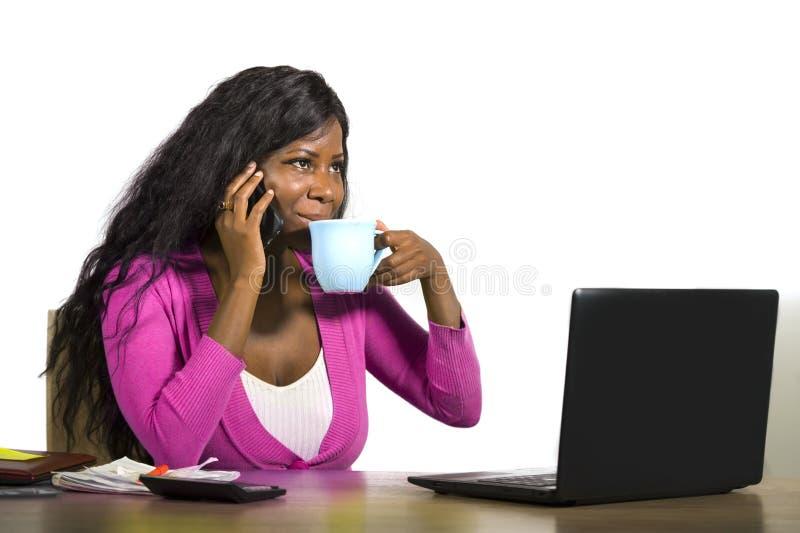 El caf? de consumici?n afroamericano trasero feliz y atractivo joven de la mujer de negocios se relaj? trabajando en casa el escr foto de archivo libre de regalías