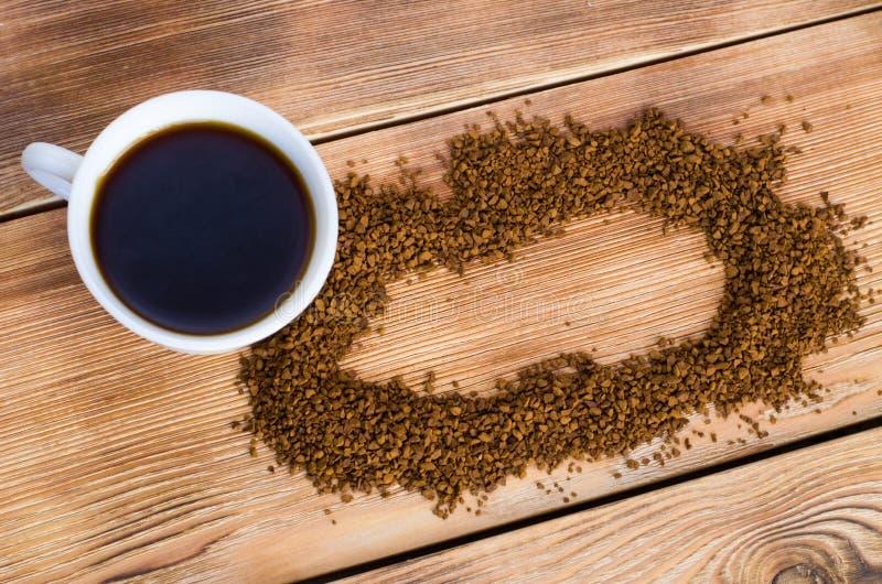 El caf? se coloca al lado de una taza blanca llenada del caf? caliente entre los granos de caf? dispersados, tabla, visi?n superi imagen de archivo libre de regalías