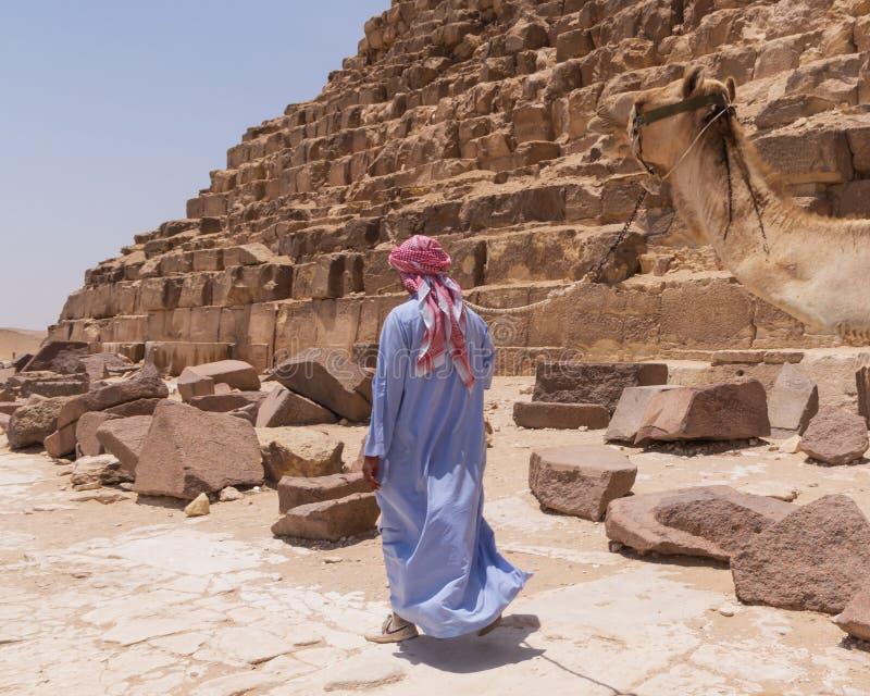 EL CAIRO, EGIPTO - 22 DE MAYO DE 2017: Hombre árabe con el camello cerca de la pirámide imagen de archivo