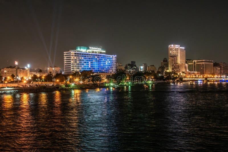 El Cairo, Egipto - 25 05 2018 - Demostración del horizonte de El Cairo Nile Ritz Carlton Hotel iluminada en la noche foto de archivo libre de regalías