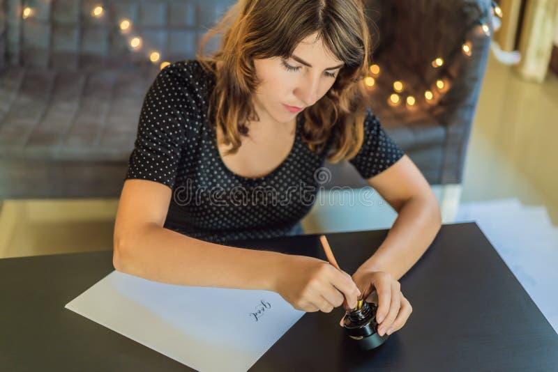El calígrafo Young Woman escribe frase en el Libro Blanco Buenos días Inscripción de letras adornadas ornamentales imagen de archivo