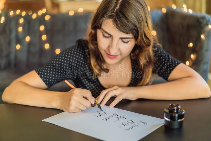 El calígrafo Young Woman escribe frase en el Libro Blanco La meta grande, determinada ideal, toma medidas Inscripción ornamental fotografía de archivo