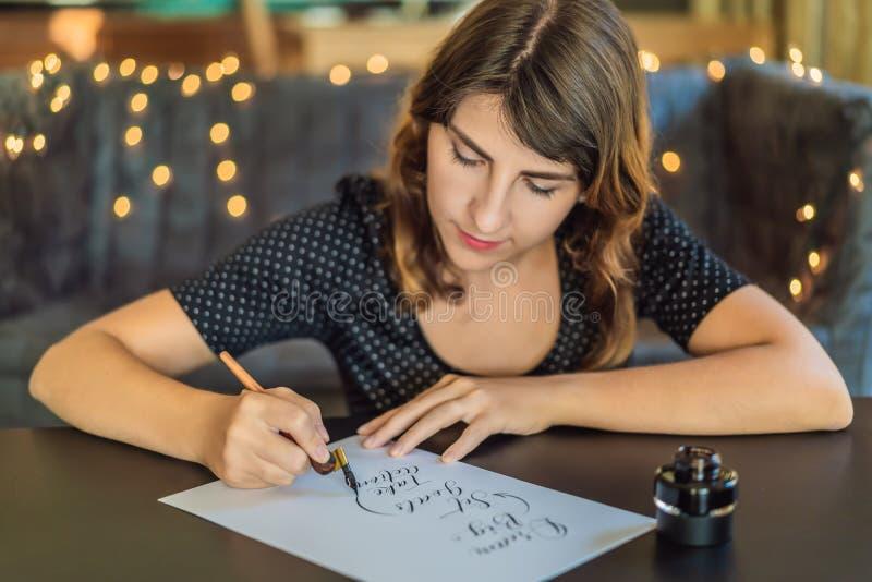El calígrafo Young Woman escribe frase en el Libro Blanco La meta grande, determinada ideal, toma medidas Inscripción ornamental imagen de archivo