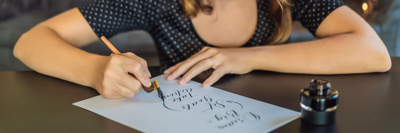 El calígrafo Young Woman escribe frase en el Libro Blanco La meta grande, determinada ideal, toma medidas Inscripción ornamental foto de archivo libre de regalías