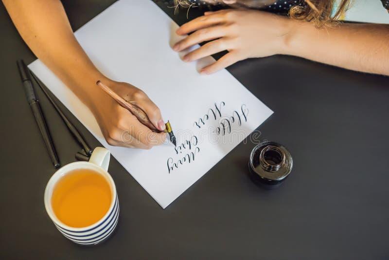 El cal?grafo Young Woman escribe frase en el Libro Blanco Inscripci?n de letras adornadas ornamentales Caligraf?a, gr?fico foto de archivo libre de regalías