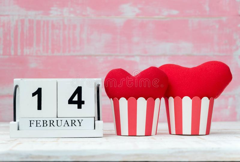 El calendario de madera el 14 de febrero, dos corazones rojos fue colocado de lado a lado y el fondo es rosado Día de tarjeta del imágenes de archivo libres de regalías
