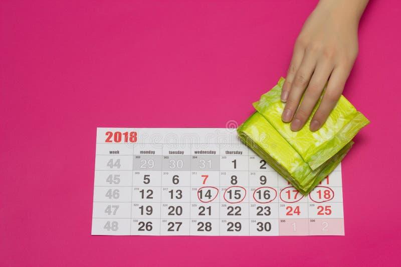El calendario y una pila de las mujeres menstruales de cojines ginecológicos, mano femenina toma un cojín, fondo rosado, espacio  foto de archivo libre de regalías