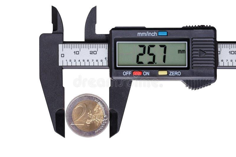 El calibrador digital con la moneda de dos euros Objetos aislados encendido imagen de archivo