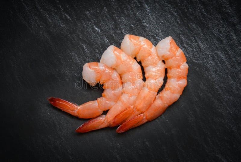 El camarón en fondo/crustáceos oscuros de los mariscos cuatro gambas de los camarones hirvió cocinado para la comida en la tabla imagen de archivo