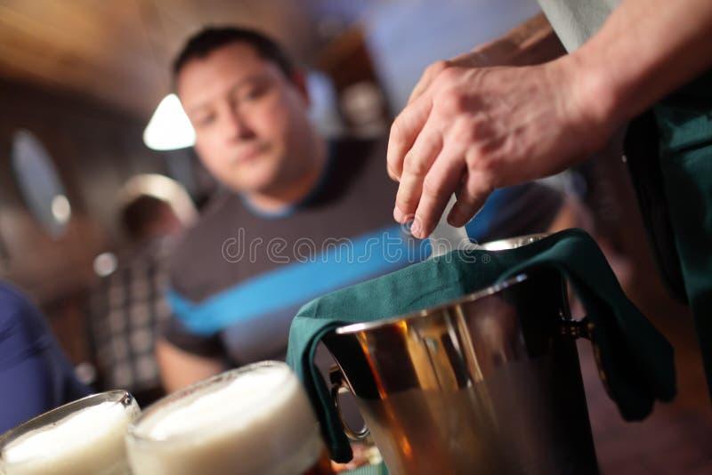El camarero abre una botella de vodka imagenes de archivo