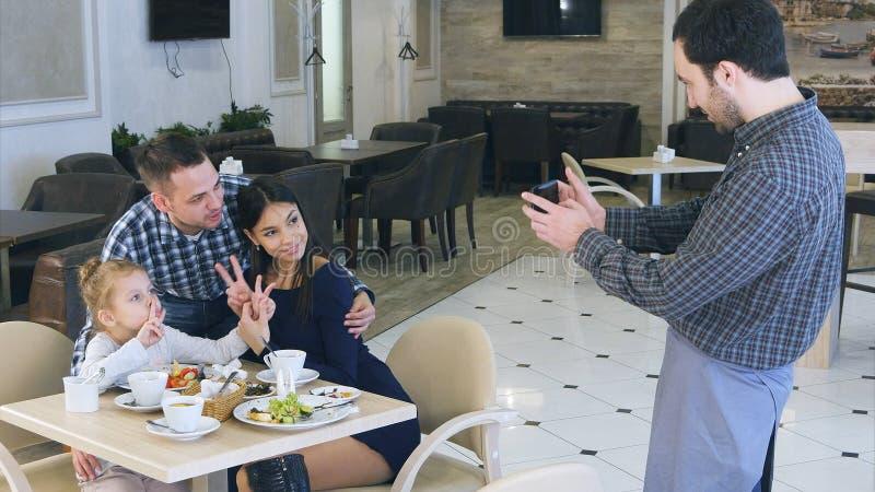 El camarero amable toma la foto de la familia joven amistosa en café en smartphone imagenes de archivo