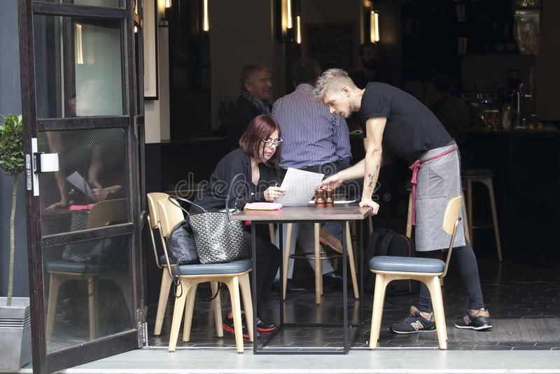 El camarero ayuda a una mujer a elegir una comida del menú foto de archivo libre de regalías