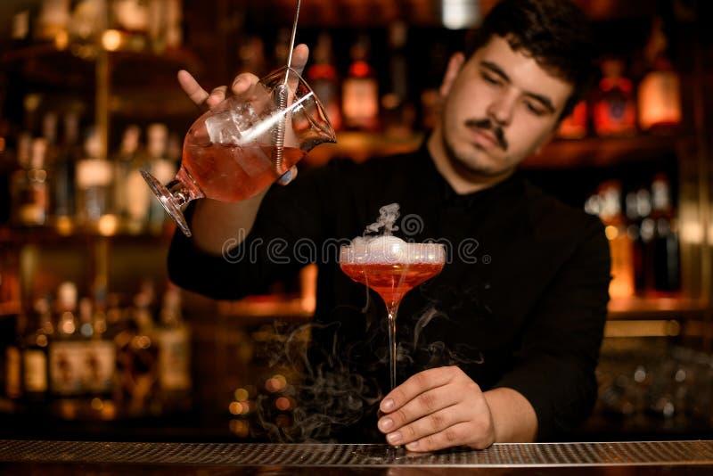 El camarero con el tamiz prepara una bebida del alcohol fotografía de archivo libre de regalías