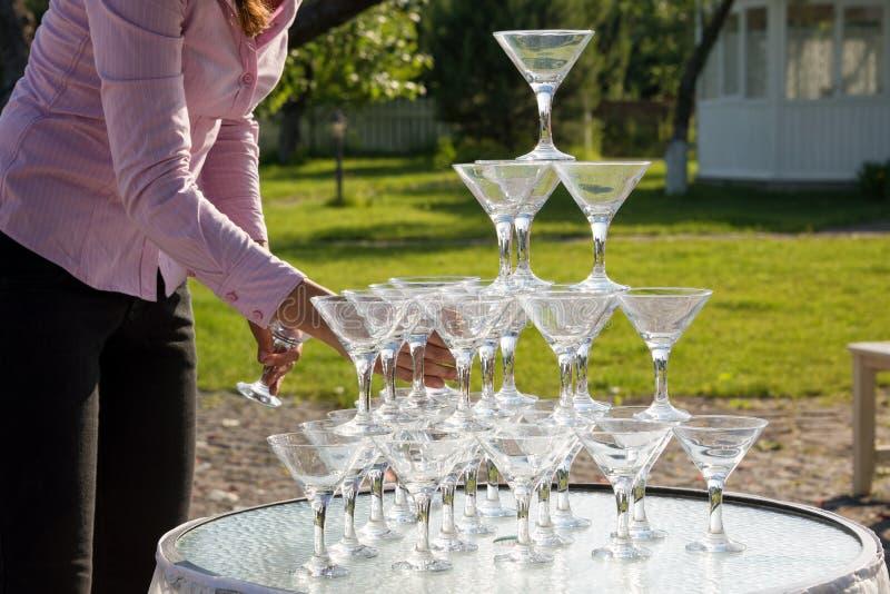 El camarero construye una pirámide de los vidrios para el champán en el jardín al aire libre en ceremonia de boda foto de archivo libre de regalías