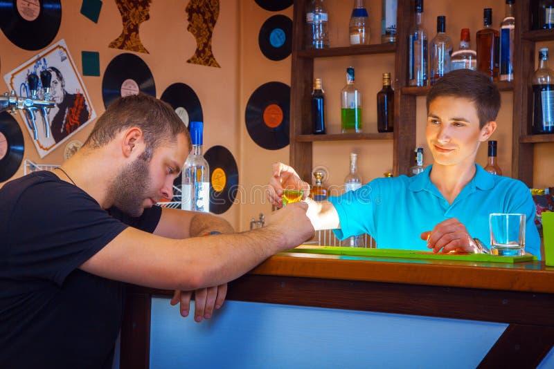 El camarero da el cóctel corto al hombre unshaved borracho en la tabla de la barra foto de archivo