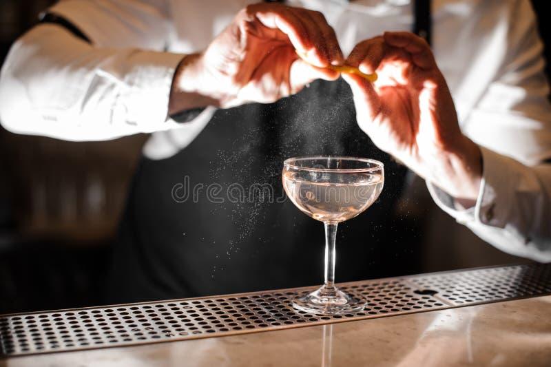 El camarero da la aspersión del jugo de la cáscara de naranja en un vidrio foto de archivo libre de regalías