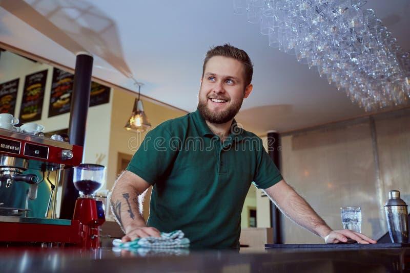 El camarero de Barista lava la superficie de la barra fotografía de archivo libre de regalías