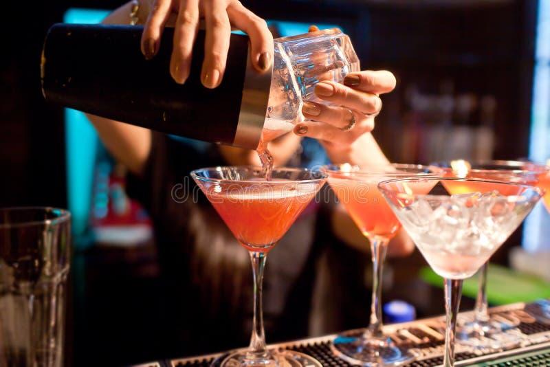 El camarero de la muchacha prepara un cóctel en el club nocturno imagen de archivo