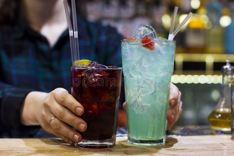 El camarero de la muchacha que lleva a cabo dos bebidas en la barra imagen de archivo libre de regalías