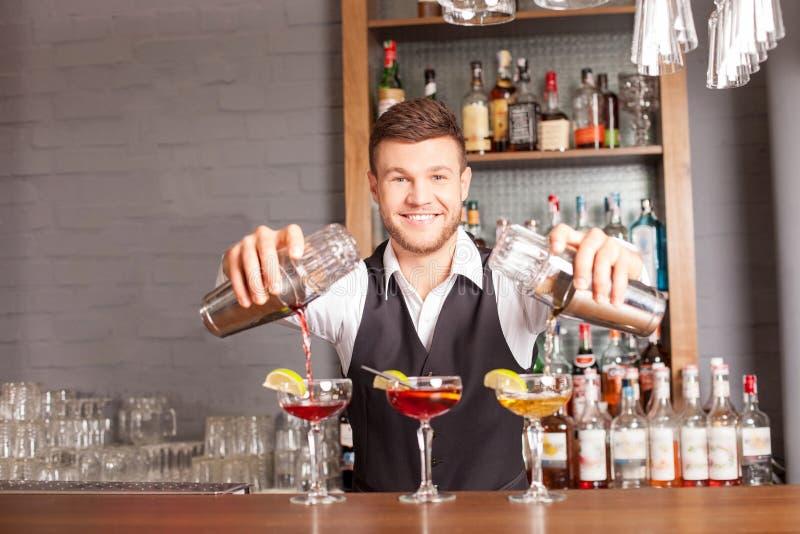 El camarero de sexo masculino alegre está mezclando la bebida en barra fotografía de archivo libre de regalías