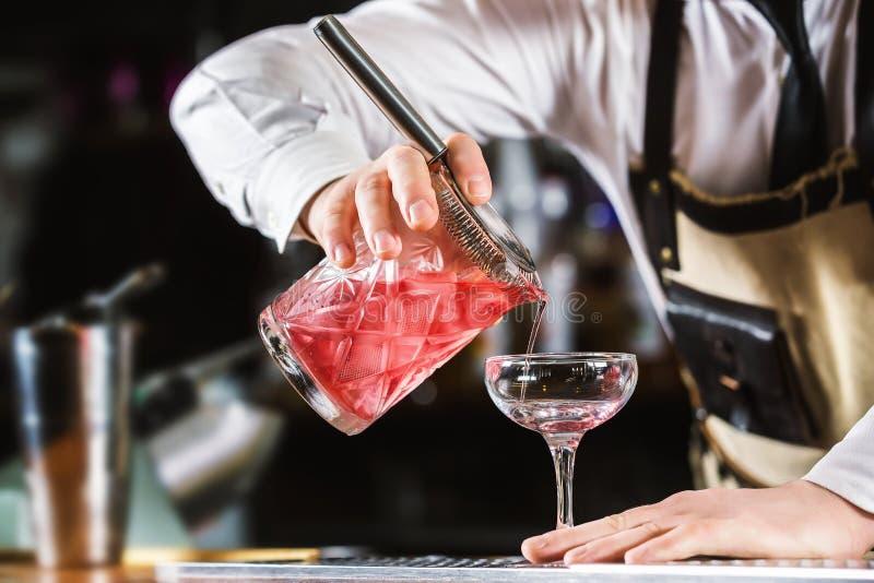 El camarero de sexo masculino está haciendo el alcohol de colada del cóctel del jarro a g fotografía de archivo libre de regalías