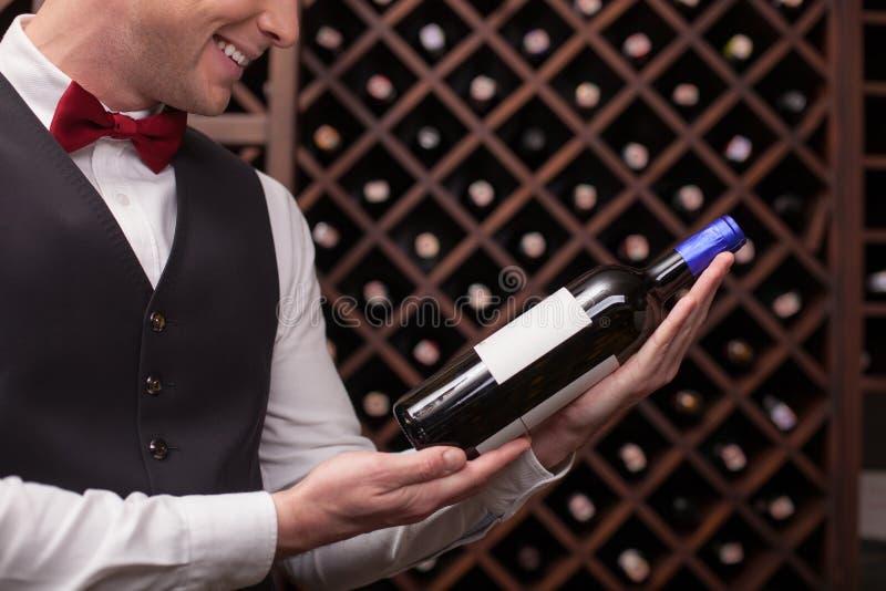 El camarero de sexo masculino lindo está eligiendo la bebida perfecta foto de archivo