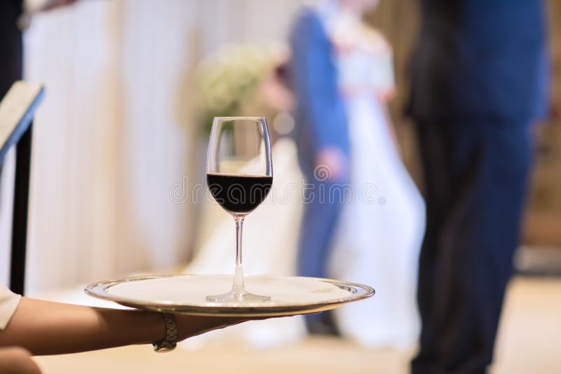 El camarero está cuidando la placa con las copas de vino rojas foto de archivo
