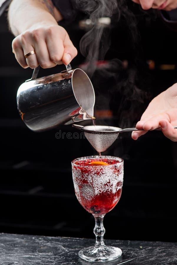 El camarero está haciendo el vino reflexionado sobre de la Navidad Vino reflexionado sobre rojo en vidrio tallado con los arándan foto de archivo libre de regalías