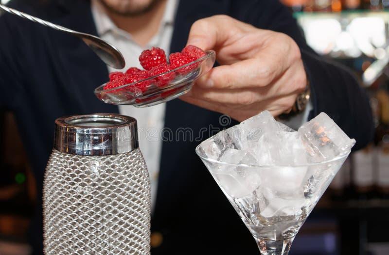 El camarero está poniendo las frambuesas frescas a una coctelera foto de archivo libre de regalías
