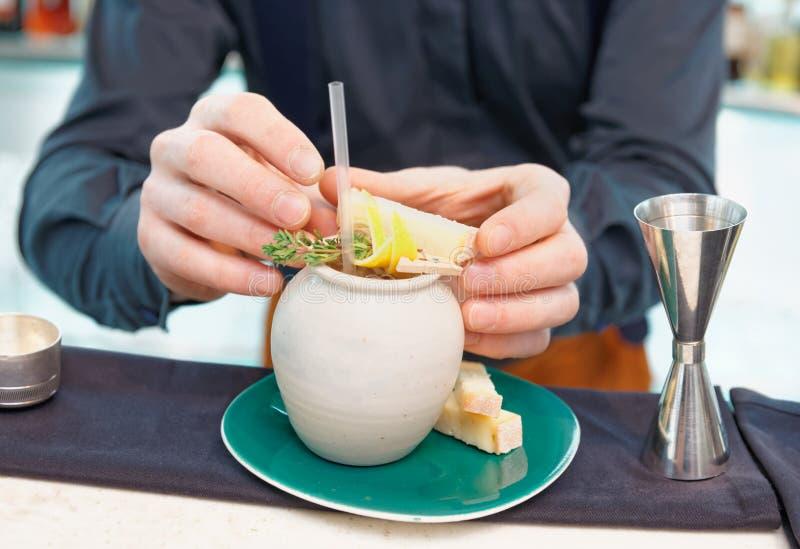 El camarero está sirviendo el queso con el cóctel imagen de archivo