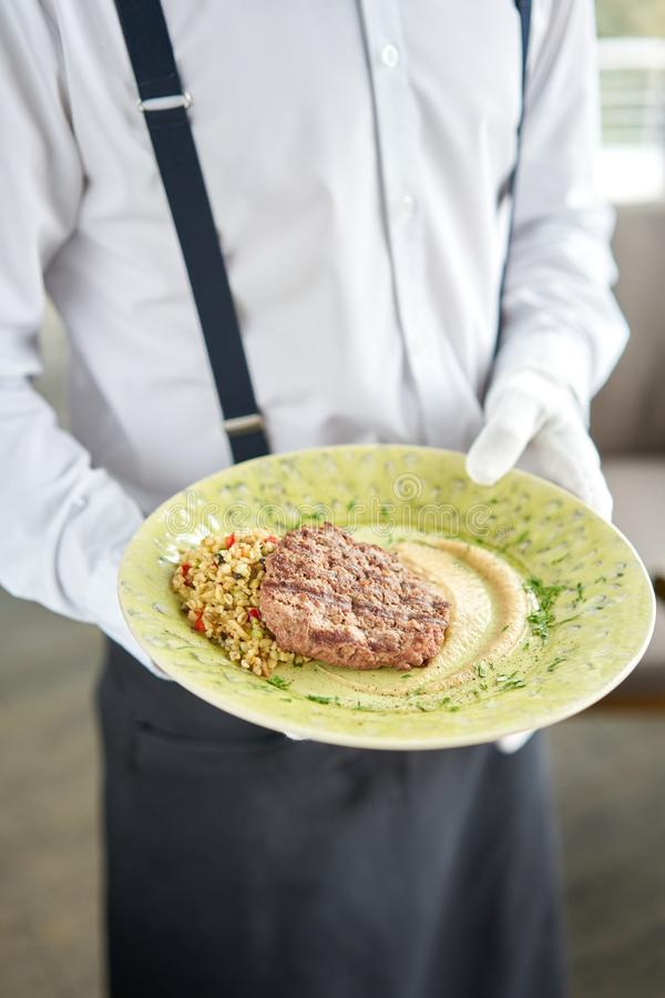 El camarero está sosteniendo un plato con carne de buey de piedra de Beefsteak, servida con bulgur y crema de cebolla ahumada Par fotos de archivo libres de regalías