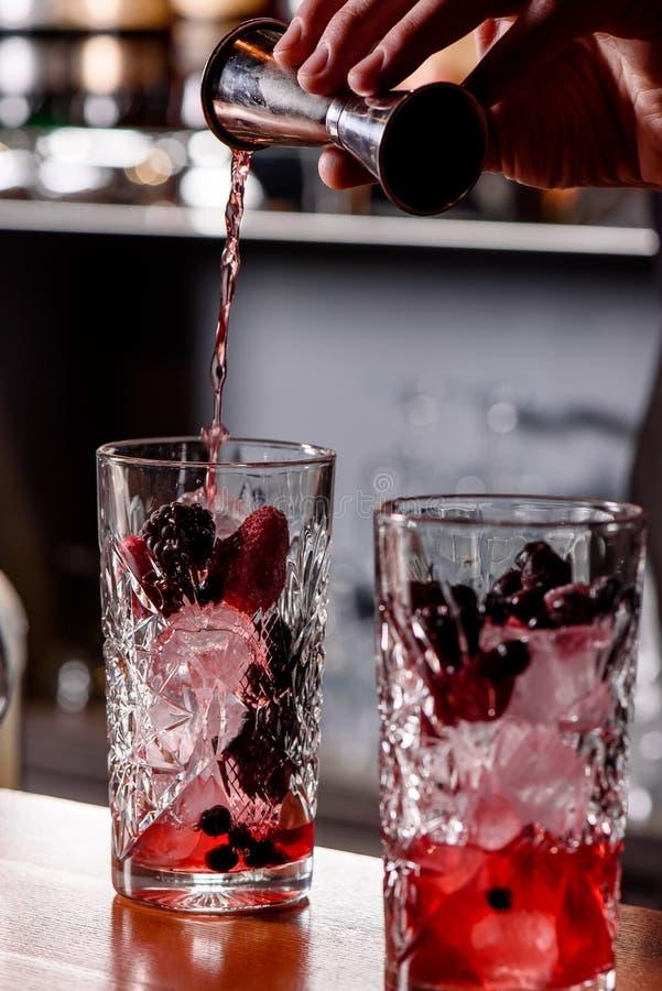 El camarero hace dos cócteles con las bayas en el primer de la barra dos vidrios con las bayas y el hielo foto de archivo