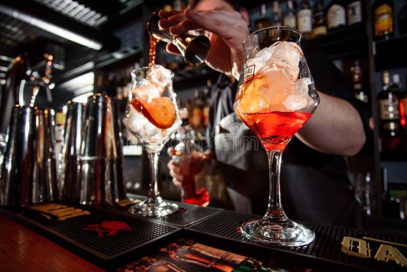 El camarero hace un cóctel hermoso en la barra El camarero azotó el cóctel imagen de archivo