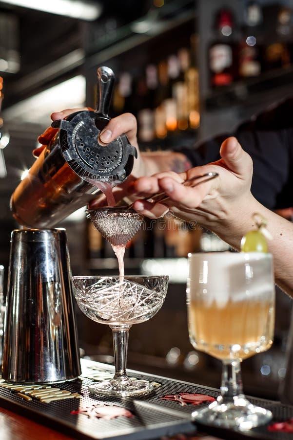 El camarero hace un cóctel hermoso en la barra El camarero azotó el cóctel imagen de archivo libre de regalías