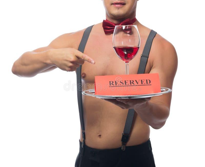 El camarero hermoso señala a un vidrio de vino rojo en una bandeja fotografía de archivo